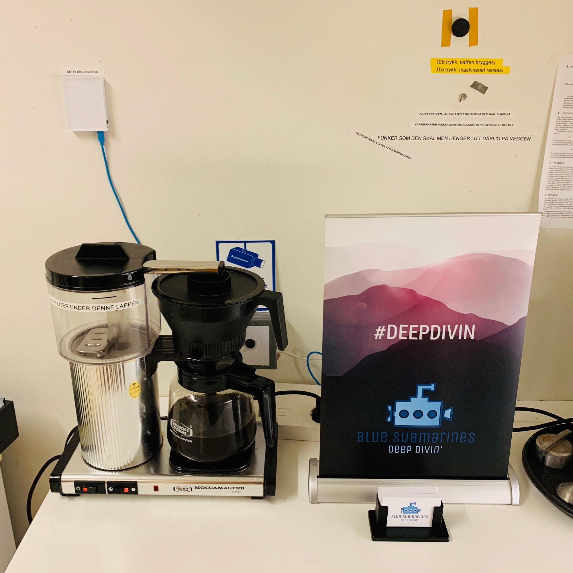 Fotografi av kjøkkenbenk med kaffetrakter og en roll-up det står deepdivin på