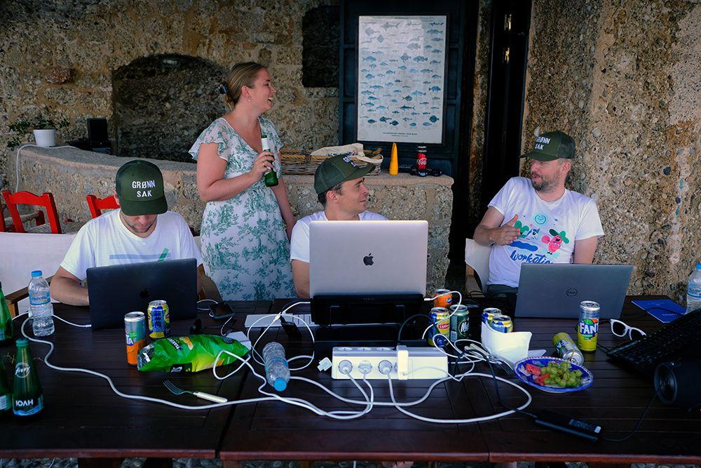 Fotografi av fire person ved et bord fylt med datautstyr