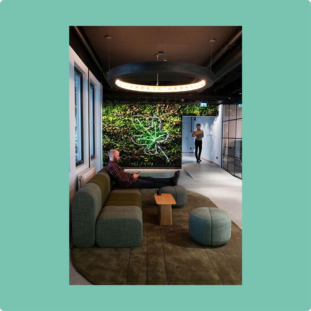 Fotografi som viser to personer på et kontor med et fikenblad på veggen