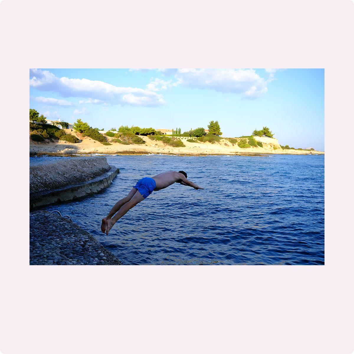 Fotografi av en person som stuper i havet fra en brygge