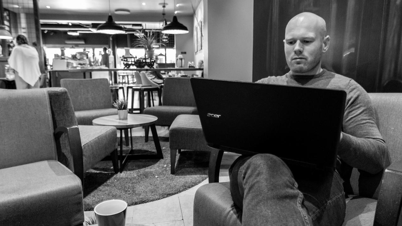 Fotografi av mann som sitter på kafe med datamaskin i fanget
