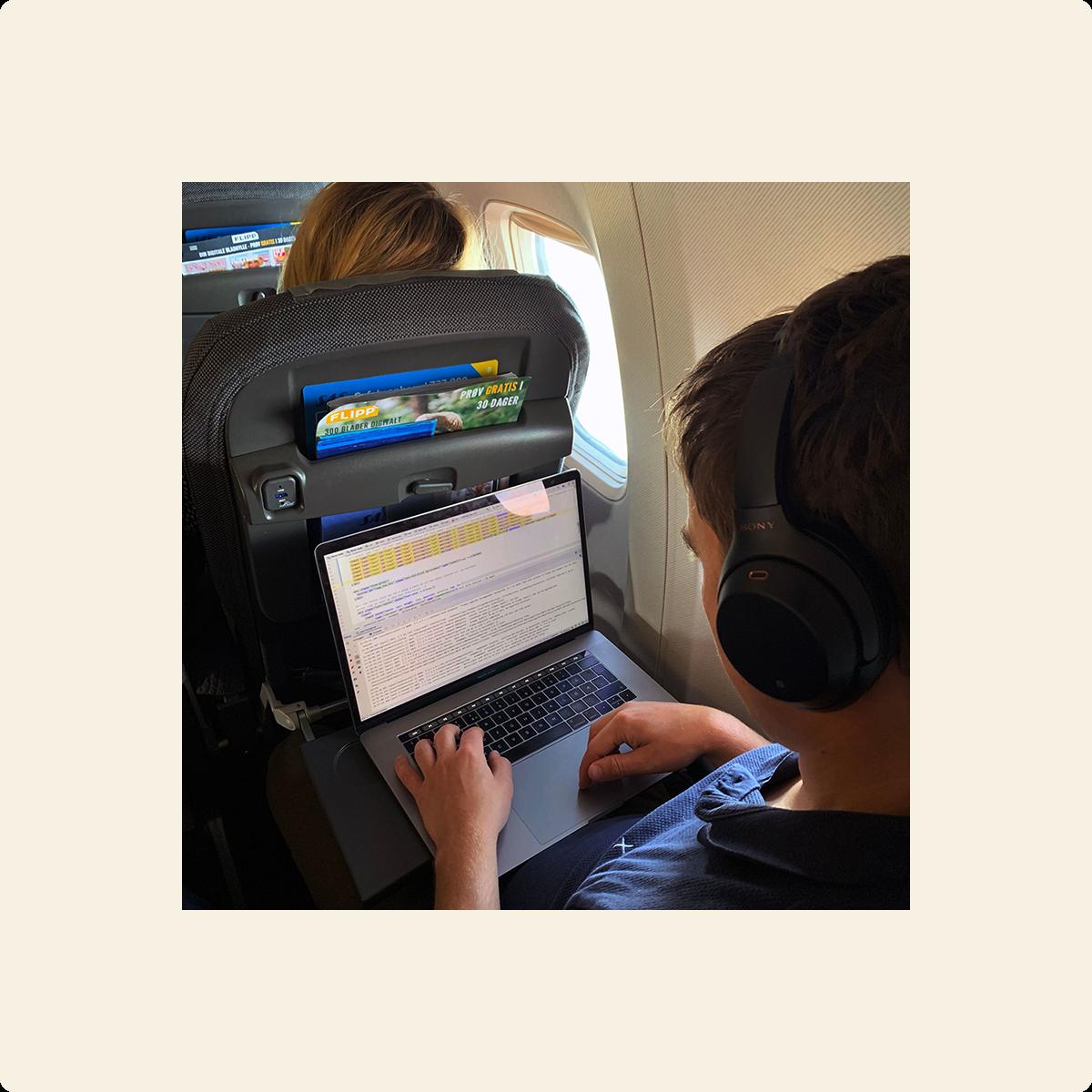 Fotografi av person på fly som sitter med datamaskin i fanget