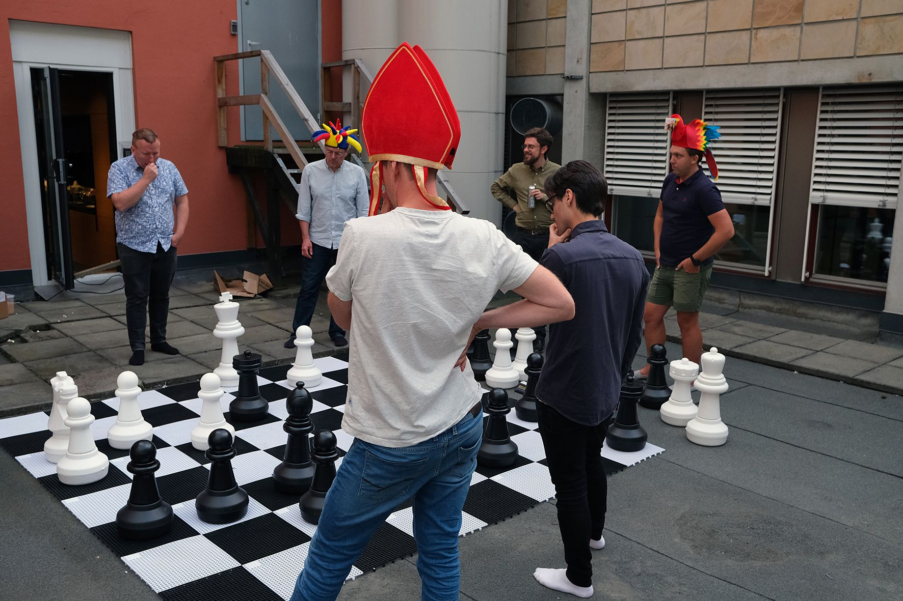 Fotografi av seks personer som står rundt et stort sjakkbrett